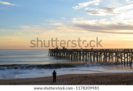 Beach with a long wooden pier at sunset; #1178209981