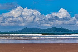 Beach with a mirror of water in the dark sand strip, a greenish sea curled by the winds, and on the horizon large cumulus clouds floating under a blue sky, floating over the Serra Do Mar mountains.