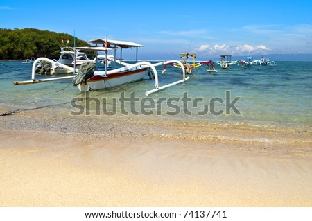 Beach with anchored traditional boats in Gili island