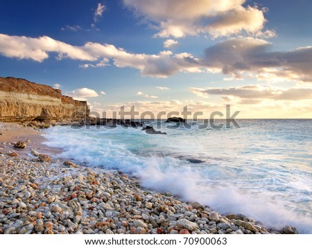 Beach with clean sand and greater wave during bright sundown