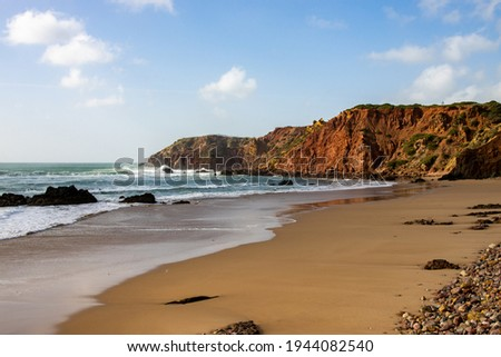 Beach with clear water and red cliffs in Algarve, Portugal Photo stock ©