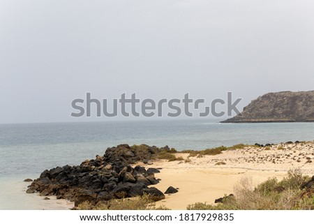 beach with mountains and cliff m in the background Stock fotó ©