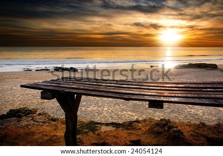 Beach with old wooden table and Sunset in the cloudy sky