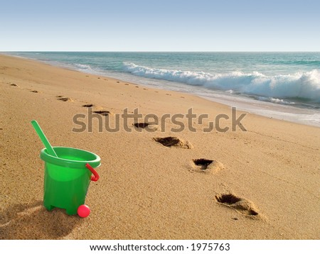Beach with plastic green bucket and footprints on sand.