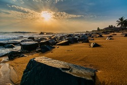 Beach with red sand and black rocks with a beautiful sunset in Congo Town, Monrovia, Liberia