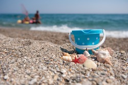 Beach with shells and plastic toys in front of the sea