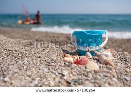 Beach with shells and plastic toys in front of the sea - stock photo