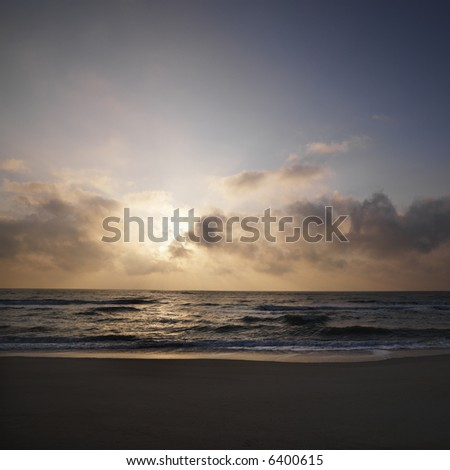 Beach with sun setting in clouds over ocean at Bald Head Island, North Carolina