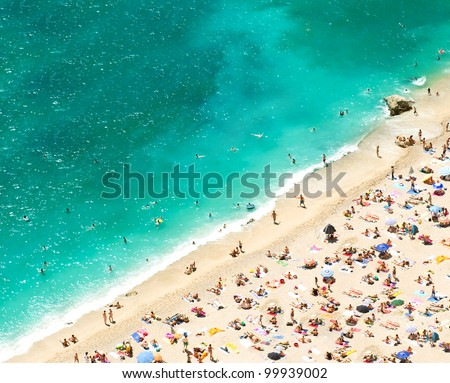 beach with tourists, sunbeds and umbrellas on the hot summer day