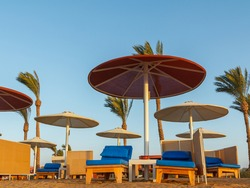 Beach with umbrellas, sunbeds and palm trees on Red Sea in Egypt. Summer time.