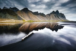 Beach with wet black sand. Picturesque and gorgeous scene. Popular tourist attraction. Location place Stokksnes cape, Vestrahorn (Batman Mountain), Iceland, Europe. Artistic picture. Beauty world.