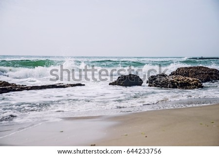 Beach with yellow sand, big rocks and beautiful waves, ocean beach, sea beach  #644233756