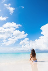 Beach woman enjoying serene luxury vacation relaxing under the sun sitting in water looking at perfect turquoise ocean at tropical getaway paradise. Girl from the back sunbathing.