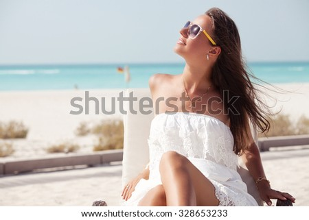 Beach woman in white dress enjoying the summer sun happy sitting in a sunbed at the tropica beach with face raised to the sunlight.