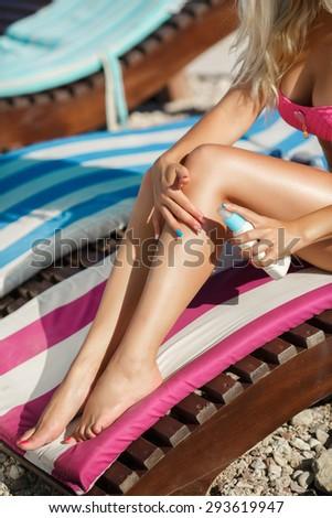 Beach woman legs with suntan lotion, vacation concept, Tan girl Applying Sunscreen on Legs, female sitting on beach and moisturizing her skin with suntan cream, beach vacation lady, series.