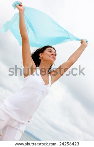 beach woman with a sarong in her hands feeling the wind