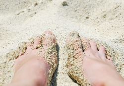Beach - women's foot and the grains of sand