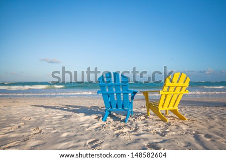 Beach wooden colorful chairs for vacations on tropical beach in Tulum, Mexico