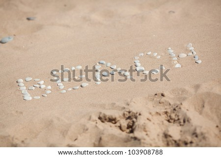 Beach word on group of stones with sand as background