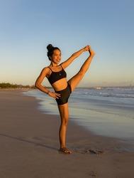 Beach yoga practice. Asian woman practicing one leg up yoga pose. Standing balancing asana. Slim body. Strong legs. Copy space. Fit and healthy. Yoga retreat. Seminyak beach, Bali, Indonesia