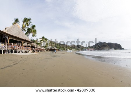 beachfront scene san juan del sur nicaragua with thatched roof restaurants and hotels on pacific ocean