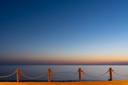 beachfront sidewalk illuminated by street lights and a calm ocean sunset behind with copy space