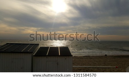 Beachhouses with sun and clouds