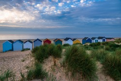 Beachhuts along the seafront and into the sand dunes an early morning in May at Southwold Suffolk East Anglia England