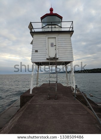 beacon light structure with dramatic sky on Lake Superior #1338509486