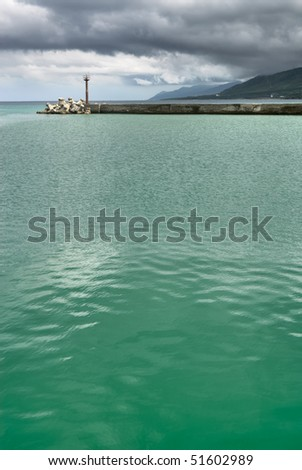 Beacon under bad weather with green water of ocean.