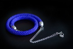 Bead crochet necklace blue color a dark surfce close up. Fashion background