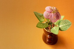 Beaded artificial house plant flower with pink petals and green leaves in pot on bright orange background with space for text. Copy space. Handicraft for home interior. Handmade crafts from beads