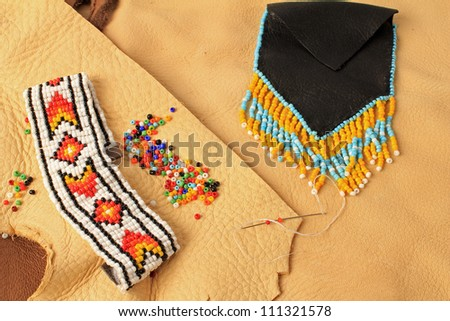 Beaded bracelet and wampum purse on assorted leather scraps  in still life setting of Native American Art.