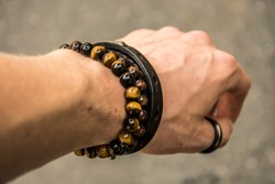 Beaded bracelets and leather bracelet on a wrist with a tungsten ring on the thumb