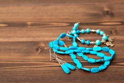 Beads and necklaces from colored semi-precious stones of turquoise and silver. Beautiful jewelry made of bright turquoise beads. Silver jewelry with precious stones on a wooden background.