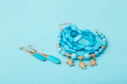 Beads and necklaces from colored semi-precious stones of turquoise and silver. Beautiful jewelry made of bright turquoise beads. Silver jewelry with precious stones on a blue background.