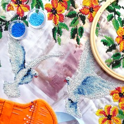 Beads embroidery of dove birds & orange flowers with leaves. Embroidery beads work on table - beads, hoop, needles. Close-up woman embroidery beads work top view two pigeon and flowers pattern