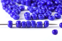 Beads spread on white background with needle. Beads with needle . Close up, macro,It is used in finishing fashion clothes. make bead necklace, beads for woman of fashion,Bead Crochet. Daily Beading.