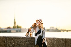 Beagle dog with content young lady in casual wear with hat hugging pet on promenade looking at each other