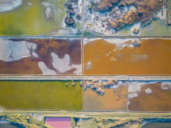 Beaituful aerial sunset view over the Pomorie Salt Ponds in Bulgaria, Black sea coast. Colorful evaporation pools with lye and healing mud on Lake Pomorie - open air SPA
