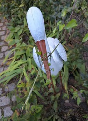 Beak of white garden sculpture of stork enlaced by green sprig of Clematis terniflora (sweet autumn clematis). Concept of the win of the nature over technology and preservation of the environment