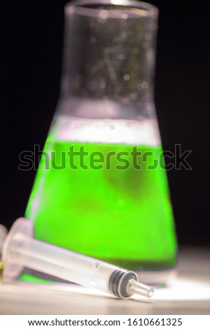 Beaker with green liquid chemical. Chemical experiment with Laboratory glass