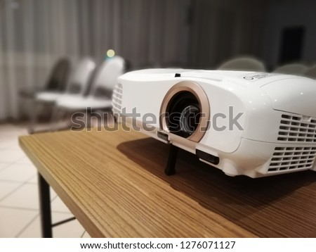 Photo of  Beamer projector in a conference hall. Chairs in background