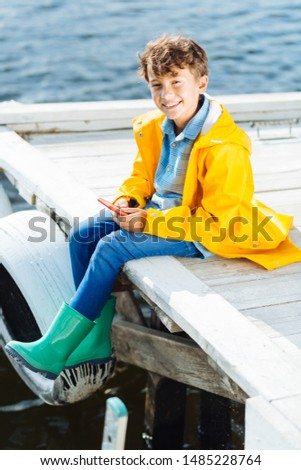 Beaming boy. Beaming boy holding phone while sitting near river wearing raincoat #1485228764