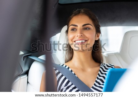 Beaming businesswoman. Beaming businesswoman holding tablet smiling while sitting in car #1494557177