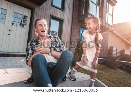 Beaming family. Beaming handsome father and cute daughter laughing while having fun outside their house #1215968056