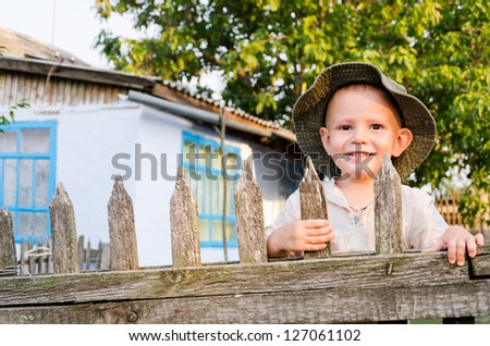Beaming happy little boy in a sunhat standing holding on to the slats of a wooden picket fence enjoying the summer sunshine