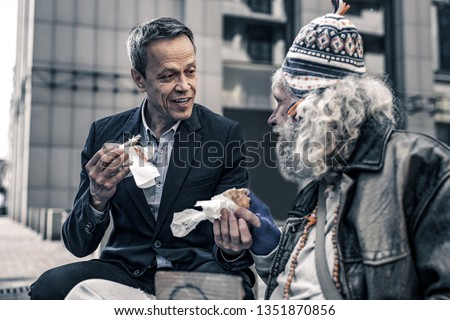 Beaming homeless. Communicative kind man talking to grey-haired senior homeless and giving him part of the sandwich