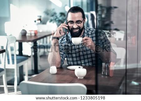 Beaming man. Beaming mature businessman feeling amazing drinking some tasty coffee having break #1233805198