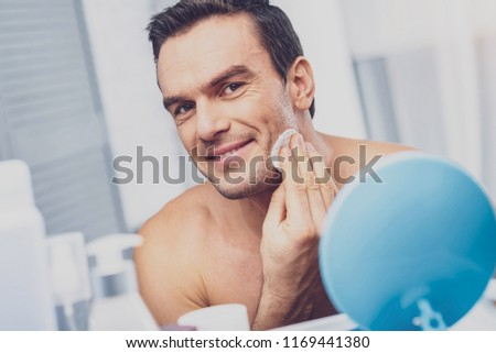 Beaming man. Beaming muscleman caring about his skin holding cotton wool in hand while standing in front of mirror #1169441380